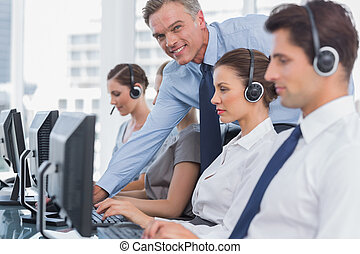 Smiling manager helping call centre employee on her computer