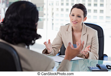 Smiling manager interviewing a male applicant in her office