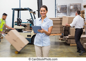 Smiling manager using digital tablet during busy period in a large warehouse