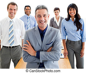 Smiling manager with folded arms in front of his team