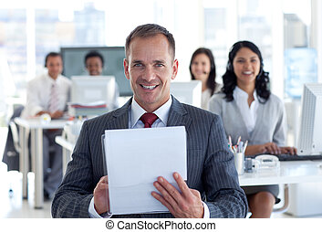Smiling manager writing notes in a call center