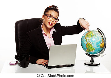 Smiling manageress pointing to a globe