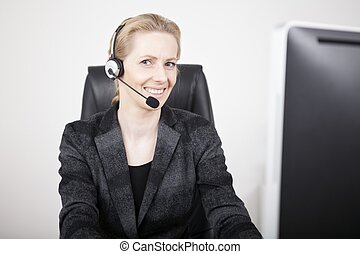 Smiling Manageress Wearing Headset at her Office