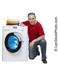 smiling mannear the washing machine and a stack of bright linen, isolated on white background