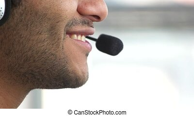 Smiling man's face talking using headset micro.
