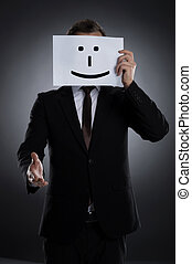 Smiling mask. Businessman holding a poster with smile on it in front of face and stretching out hand