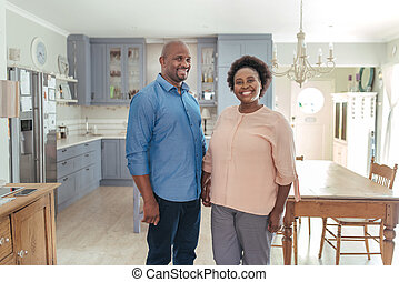 Smiling mature African couple standing together in their kitchen