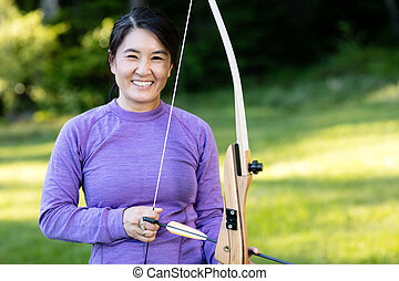 Smiling Mature Athlete Holding Bow And Arrow In Forest