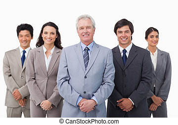 Smiling mature businessman standing with his team