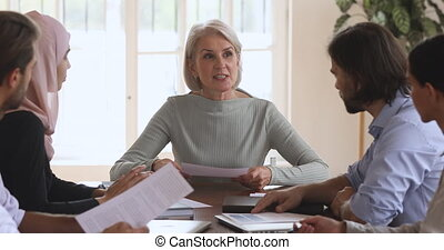 Smiling mature businesswoman sitting at table, consulting teaching instructing young multiracial interns colleagues in office. Happy smart older female team leader holding meeting with employees.