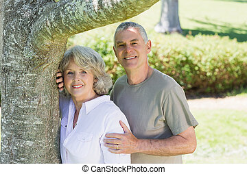 Smiling mature couple besides tree at park - Portrait of a...