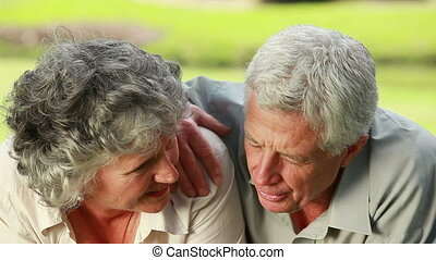 Smiling mature couple lying on the grass