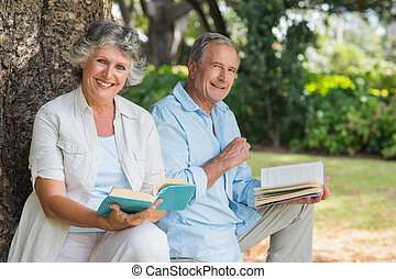 Smiling mature couple reading books together