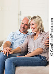 Smiling mature couple sitting on sofa