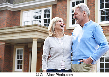 Smiling Mature Couple Standing Outside Home