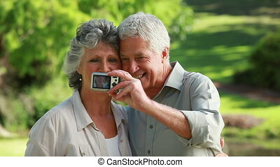 Smiling mature couple taking themselves in picture in the...