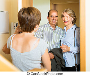 Smiling mature family couple visiting daughter