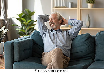 Smiling mature man dreaming, relaxing on cozy couch