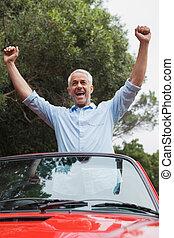 Smiling mature man enjoying his red convertible