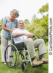 Smiling mature man in wheelchair with partner