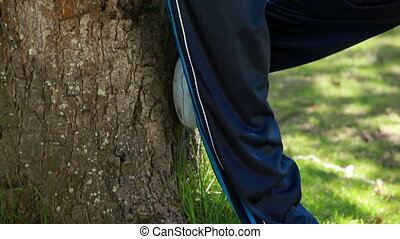 Smiling mature man leaning against a tree in sportswear