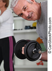 Smiling mature man lifting barbell