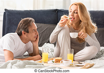 Smiling mature man looking at beautiful woman eating pancakes in bed