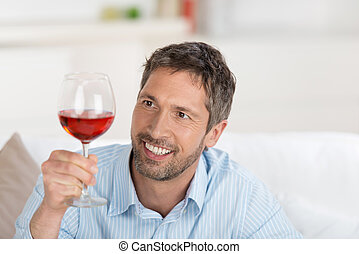 Smiling Mature Man Looking At Wineglass At Home - Portrait...