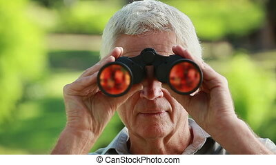Smiling mature man looking through binoculars