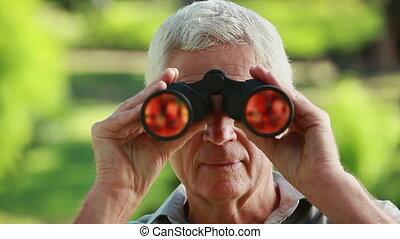 Smiling mature man looking through binoculars