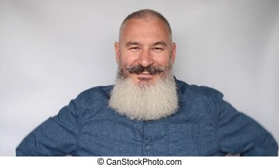 Smiling mature man on grey background. Portrait of senior man flirting and blinking eye. Aged macho man.