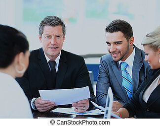 Smiling mature man sitting at a business meeting with colleagues.