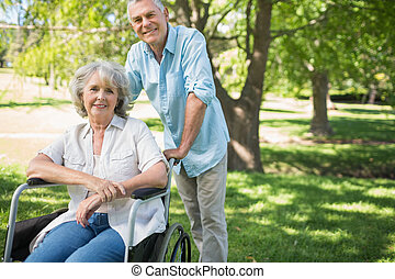 Smiling mature man with woman sitting in wheel chair at park...