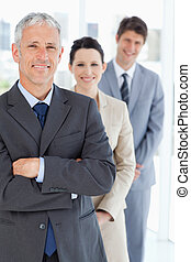 Smiling mature manager standing upright in front of his young business team