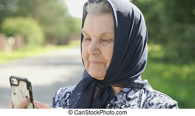 Smiling mature old woman shows smartphone outdoors