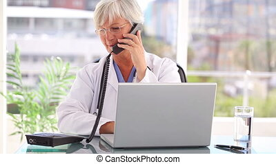 Smiling mature practitioner using her phone