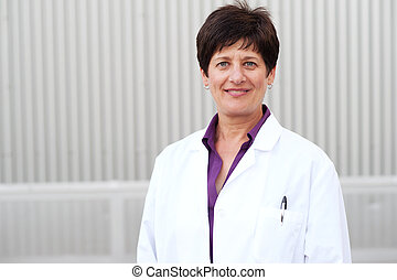 Smiling mature professional woman dressed in labcoat ...