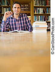 Smiling mature student studying at desk in the library