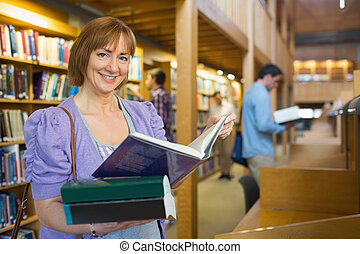 Smiling mature student with men in the background at library