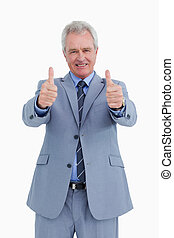 Smiling mature tradesman giving his thumbs up against a...