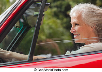 Smiling mature woman driving red convertible on sunny day