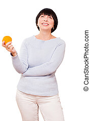 Smiling mature woman holding orange