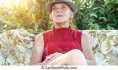 Smiling mature woman in hat sitting in the garden smoking cigarette. 3840x2160. 4k