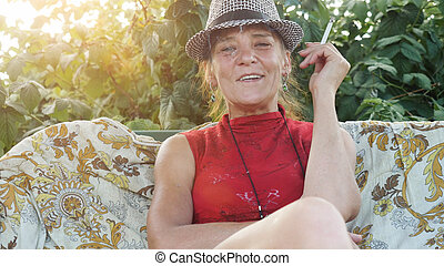 Smiling mature woman in hat sitting in the garden smoking cigarette.