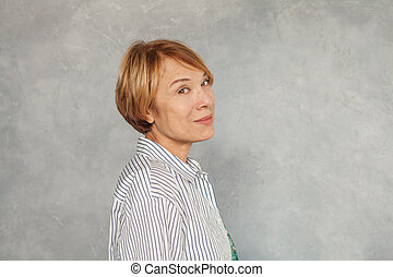 Smiling mature woman on gray background
