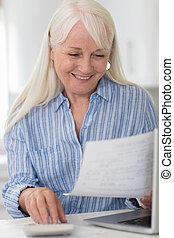 Smiling Mature Woman Reviewing Domestic Finances