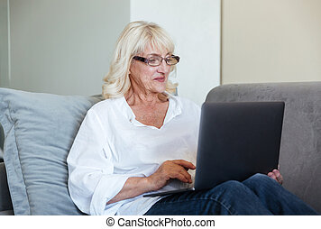 Smiling mature woman using laptop computer
