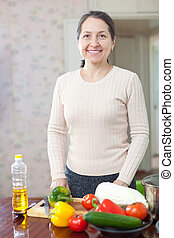 mature woman with vegetables at her kitchen