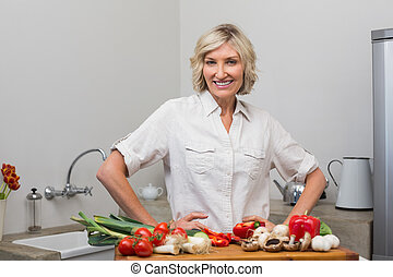 Smiling mature woman with vegetables in kitchen
