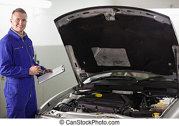 Smiling mechanic holding a clipboard